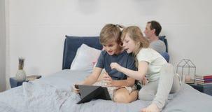 Dzieci używa pastylkę są ubranym rzeczywistość wirtualna szkła w sypialni, rodzina wpólnie ma zabawę w domu podczas gdy macierzys zbiory wideo