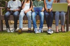 Dzieci używa technologie przy parkiem zdjęcie royalty free