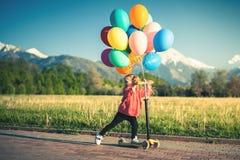 Dzieci uczą się jechać hulajnoga w parku na pogodnym letnim dniu Preschooler dziewczyna w zbawczym hełmie i fotografia stock