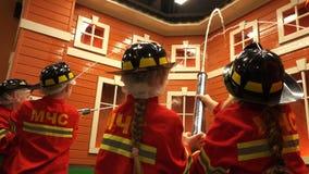 Dzieci uczą się zawód strażak i palacze gaszą płomienie sztuczni bagażniki na modelują dom zbiory wideo