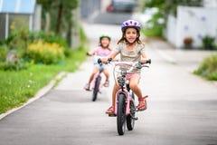 Dzieci uczy się jechać bicykl na podjeździe outside Fotografia Stock