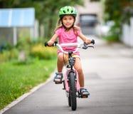 Dzieci uczy się jechać bicykl na podjeździe outside Zdjęcia Royalty Free