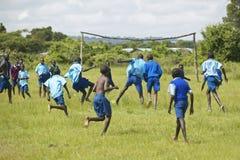 Dzieci w błękitnych mundurach bawić się piłkę nożną przy szkołą blisko Tsavo parka narodowego, Kenja, Afryka Zdjęcia Royalty Free
