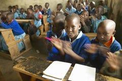 Dzieci w błękitnych mundurach przy szkołą za biurkiem blisko Tsavo parka narodowego, Kenja, Afryka Zdjęcia Royalty Free