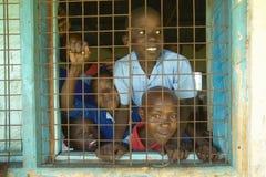 Dzieci w błękitnych mundurach w okno przy szkołą blisko Tsavo parka narodowego, Kenja, Afryka Zdjęcie Royalty Free