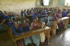 Dzieci w błękitnych mundurach w szkole za biurkiem blisko Tsavo parka narodowego, Kenja, Afryka Fotografia Royalty Free