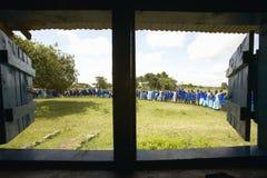Dzieci w błękitnym uszeregowaniu przy szkołą przez wnętrza okno w schoolroom blisko Tsavo parka narodowego, Kenja, Afryka Obrazy Royalty Free