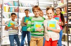Dzieci w bibliotecznych chwyta ćwiczenia książkach i stojaku Fotografia Royalty Free