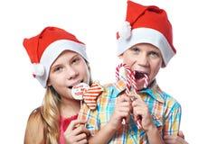 Dzieci w czerwonych nakrętkach z Bożenarodzeniowymi cukierkami odizolowywającymi Zdjęcie Stock