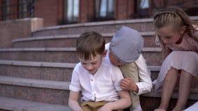 Dzieci w eleganckim retro ubrania szukali przygody na ulicie Piękni dzieci przy starą cegłą zbiory wideo