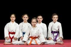 Dzieci w kimonowym obsiadaniu na tatami na sztukach samoobrony seminaryjnych Selekcyjna ostrość obraz stock