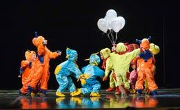 Dzieci w śmiesznych barwionych kombinezonów obcych tanczy na scenie Fotografia Stock