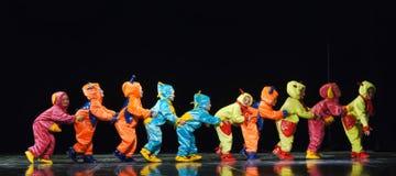 Dzieci w śmiesznych barwionych kombinezonów obcych tanczy na scenie Obrazy Stock