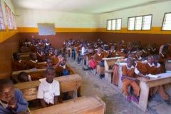 Dzieci w mundurach w szkoły podstawowej sala lekcyjnej listetning nauczyciel w obszarze wiejskim blisko Arusha, Tanzania, Afryka Fotografia Royalty Free