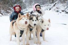 Dzieci w narciarskich kostiumów psa drużyny husky fotografia royalty free