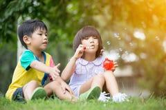 Dzieci w parkowych podmuchowych mydlanych bąblach zdjęcia royalty free