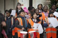 Dzieci w pomarańczowych waistcoats śpiewają kolęda, zbierają pieniądze dla dobroczynności obrazy royalty free