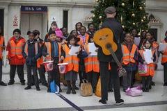 Dzieci w pomarańczowych waistcoats śpiewają kolęda, zbierają pieniądze dla dobroczynności fotografia stock