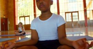 Dzieci w wieku szkolnym wykonuje joga na ćwiczenie macie w szkole 4k zbiory