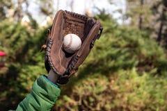 Dzieci wręczają z baseglove mienia baseballa piłką w zamazanym tle zdjęcia royalty free