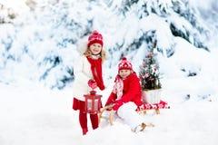 Dzieci z choinką Śnieżna zimy zabawa dla dzieciaków Zdjęcia Stock