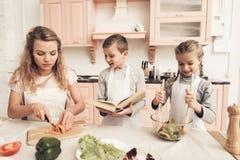 Dzieci z matką w kuchni Dzieciaki pomagają matki robić sałatki zdjęcia royalty free