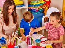 Dzieci z nauczyciel kobiety obrazem na papierze w dziecinu Zdjęcie Stock