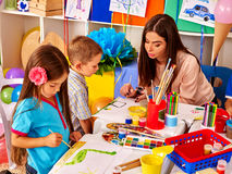 Dzieci z nauczyciel kobiety obrazem na papierze wewnątrz Zdjęcie Royalty Free