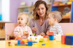 Dzieci z nauczycielem bawić się edukacyjne zabawki, sztaplowanie i ułożenie kolorowi kawałki Uczący się przez doświadczenia pojęc fotografia royalty free
