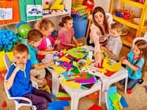 Dzieci z nauczycielem robią coś z barwionego papieru Fotografia Royalty Free