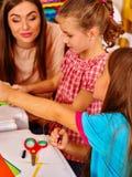 Dzieci z nauczycielem robią coś z barwionego papieru Obrazy Royalty Free