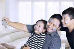 Dzieci z ojcem bierze fotografię wpólnie w domu obrazy stock