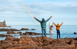 Dzieci z ojcem blisko morza są szczęśliwi z tęczą Co zdjęcia stock