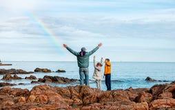 Dzieci z ojcem blisko morza są szczęśliwi z tęczą Co fotografia stock