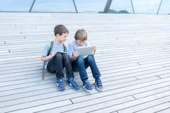 Dzieci z pastylka komputerami plenerowymi Ludzie edukacja uczenie technologii czasu wolnego pojęcia Obrazy Royalty Free