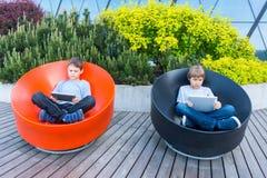 Dzieci z pastylka komputerami plenerowymi Ludzie edukacja uczenie technologii czasu wolnego pojęcia Obrazy Stock