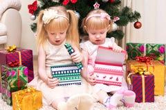 Dzieci z prezentami zbliżają choinki Obrazy Royalty Free