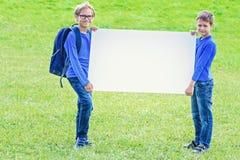 Dzieci z pustą białą plakat deską outdoors zdjęcie royalty free
