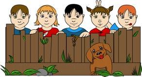 Dzieci za ogrodzeniem z psem i trawą obrazy royalty free