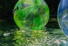 Dzieci zabawę wśrodku plastikowych balonów na wodzie Obrazy Stock