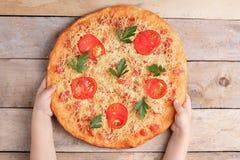 Dzieciaków chwytów Margarita pizza z pomidorem i dwa czerwieni chili na popielatym stole, odgórnym widoku i miejscu dla teksta, obraz stock