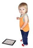 Dzieciaków koszty o pastylka pececie, który kłama na podłoga. Obraz Royalty Free