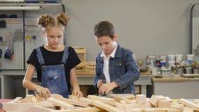 Dzieciaków mistrzowie w warsztacie Mały budowniczego pojęcie Dzieci pracuje w ciesielce chłopiec młotkuje gwóźdź w drewnianej des zbiory