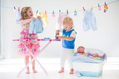 Dzieciaków odprasowywać odziewa dla dziecko brata Zdjęcia Royalty Free