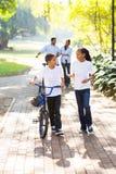 Dzieciaków rodzice chodzi parka zdjęcia stock