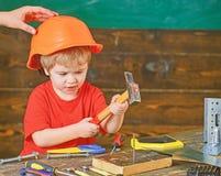 Dzieciak bawić się z młotem Ojczulka mienia hardhat na syn głowie Skoncentrowany dzieciak w warsztacie obraz stock
