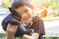 Dzieciak bawić się dziecko królika Obrazy Royalty Free