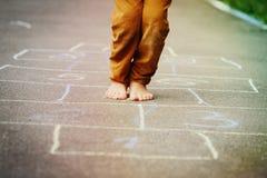 Dzieciak bawić się hopscotch na boisku Obraz Stock