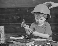 Dzieciak bawić się z młotem Ojczulka mienia hardhat na syn głowie Skoncentrowany dzieciak w warsztacie fotografia stock