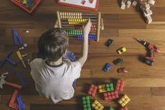 Dzieciak bawić się z zabawkami Chłopiec obsiadanie na drewnianej podłoga Odgórny widok Zdjęcie Royalty Free